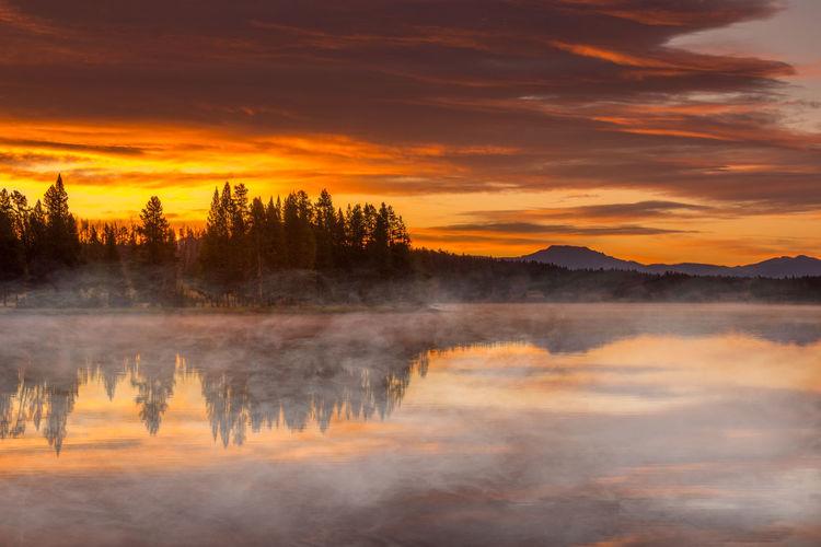 Burning sky, sunrise and morning fog at the lake. yellowstone national park
