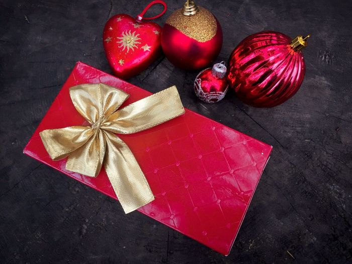 Christmas gift wrapped in red paper with golden ribbon surrounded by multiple red and golden christmas globes Christmas Present Gift Holiday Winter Celebrate Red Ribbon Wrapped Wooden Table Rustic Indoors  No People Globes Shining Bright Decorations Christmas Globes Golden Ribbon Surprise