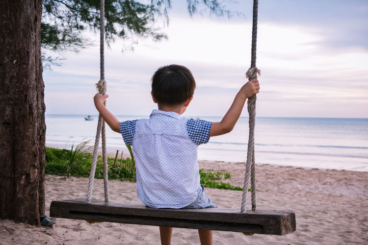 Rear view of boy swinging on rope swing at beach
