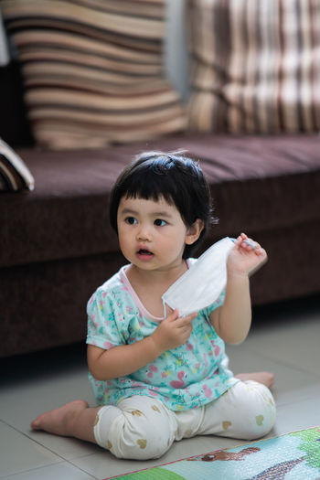 Cute baby girl sitting at home