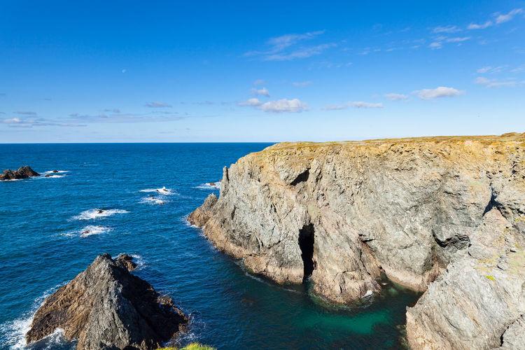 Rocks on sea shore against blue sky