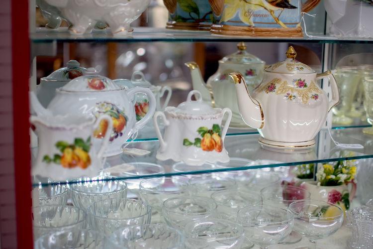 Pretty display of antique wine glasses and fancy porcelain tea pots