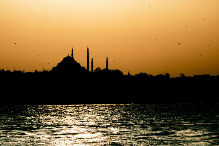 Silhouette of mosque against sky during sunset