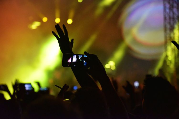 Silhouette of person holding mobile phone at concert