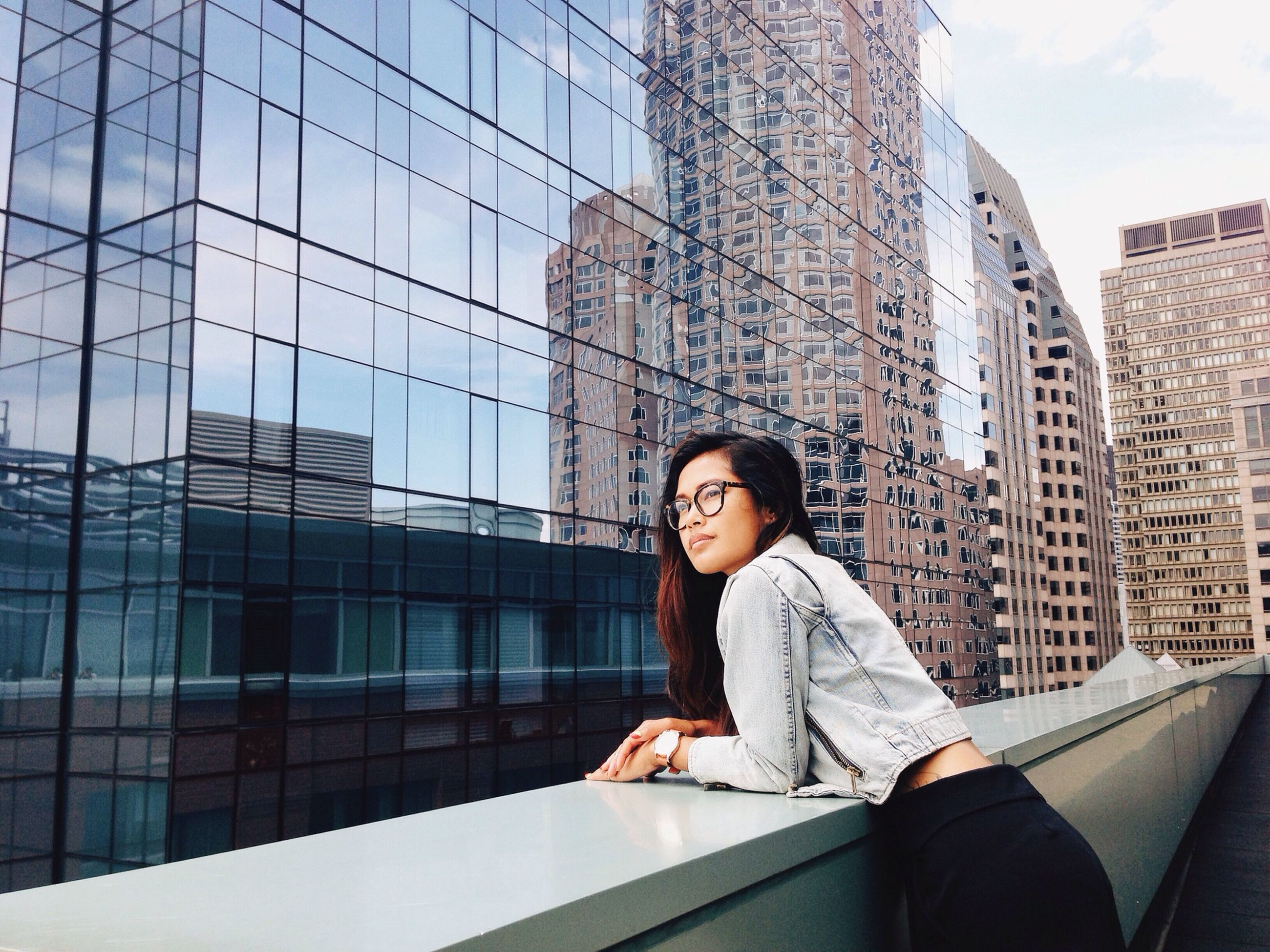 building exterior, architecture, built structure, lifestyles, person, young adult, casual clothing, window, leisure activity, sky, waist up, front view, portrait, looking at camera, day, city, low angle view, outdoors