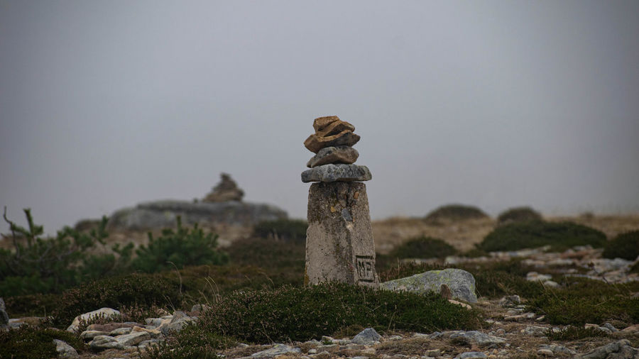 Stack of stones on field against sky