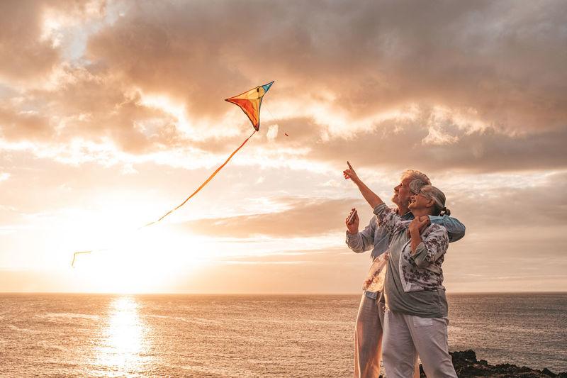 Senior couple flying kite while standing at beach against sky