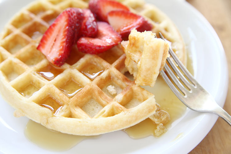 Close-up of strawberries on waffle in plate over table