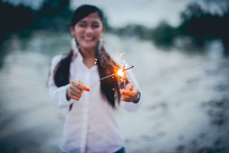 Cheerful Woman Holding Lit Sparklers At Lakeshore