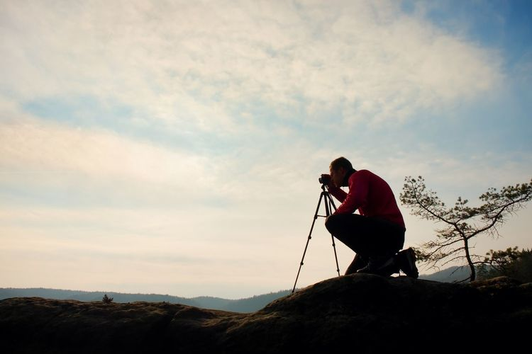 Amateur photographer takes photos with mirror camera on peak of rock. dreamy fogy landscape,