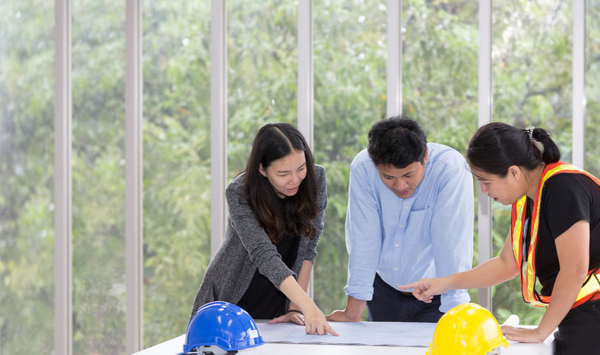 Coworkers discussing blueprint on table while standing against window in office