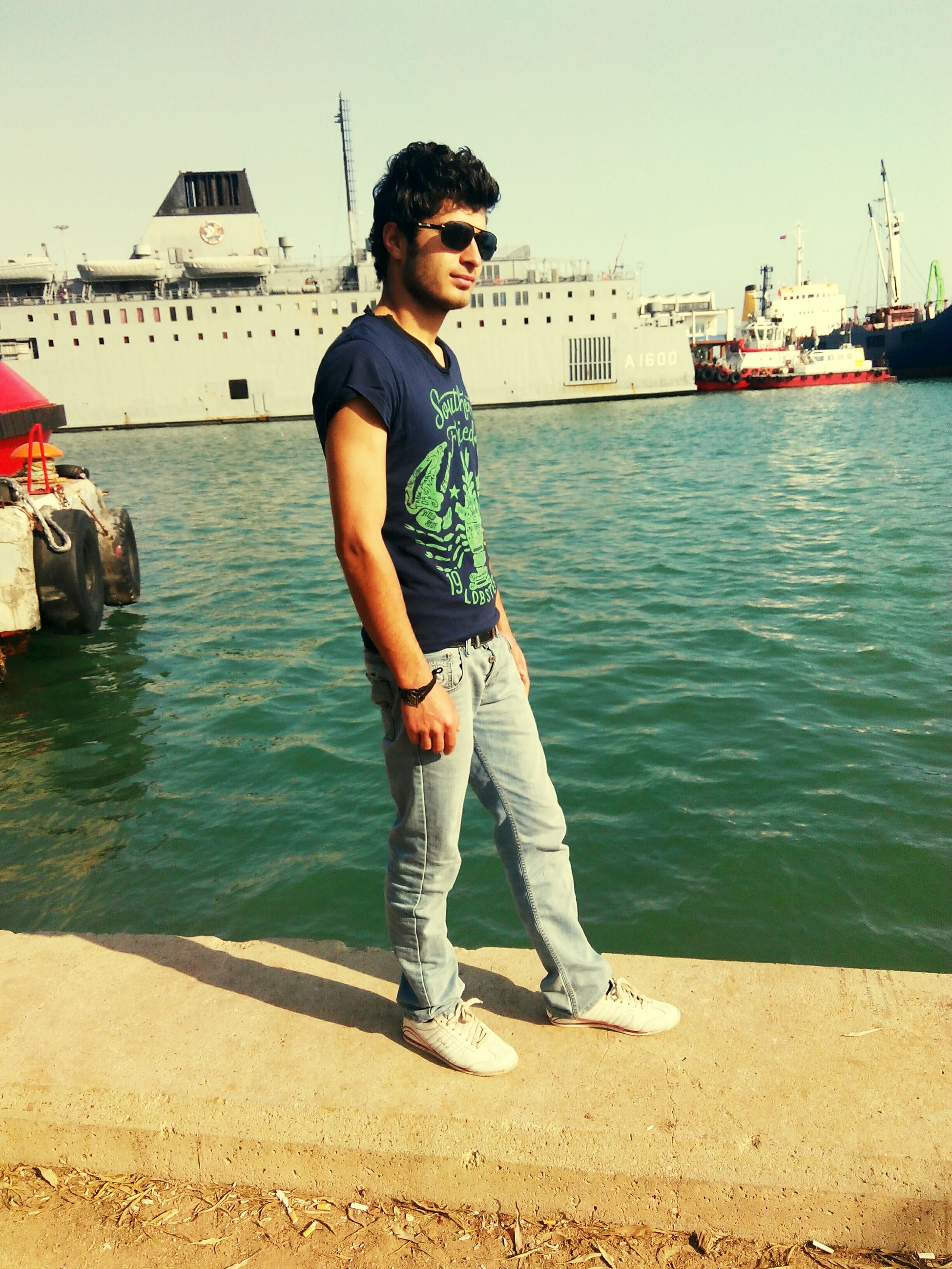 water, person, casual clothing, lifestyles, full length, young adult, leisure activity, nautical vessel, young men, sea, standing, transportation, sunglasses, front view, smiling, portrait, sky, looking at camera