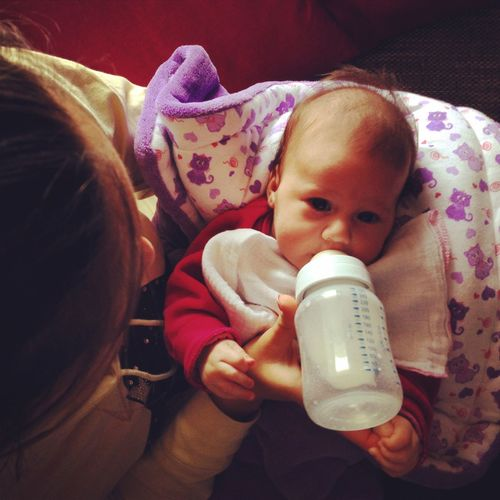 High angle view of mother feeding baby girl from bottle