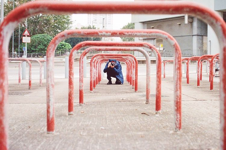 Man photographing below bicycle rack