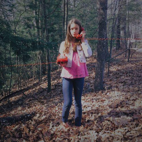Teenage girl using landline phone in forest