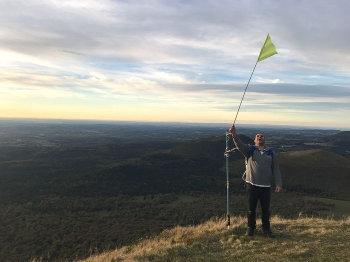 Man waving flag on mountain against sky