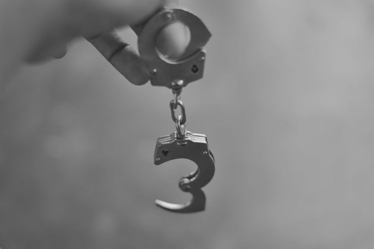 Close-up of hand holding chain hanging from metal