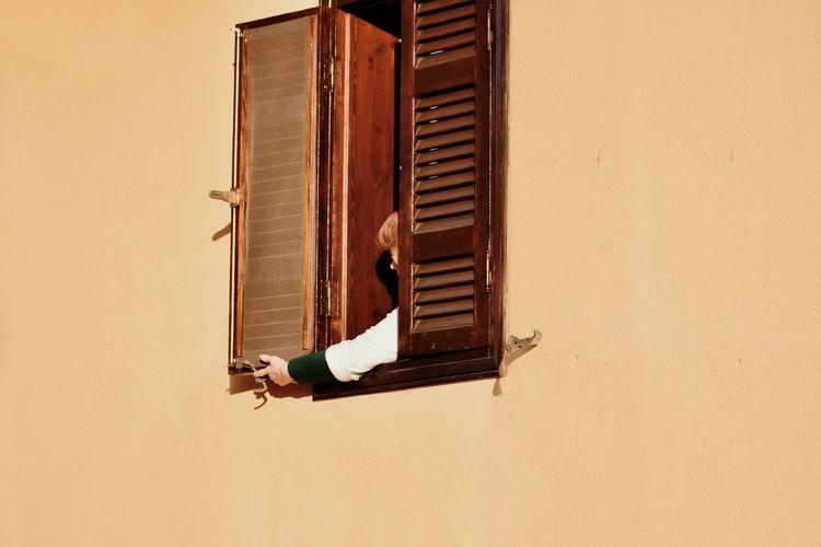 Senior woman closing window in house