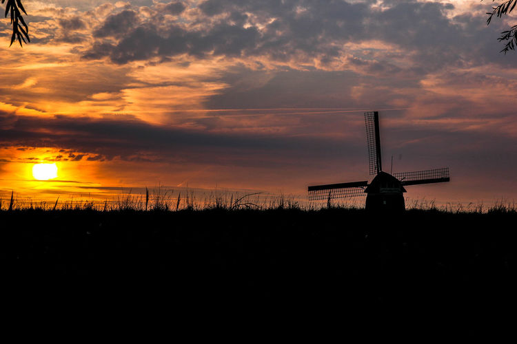 Silhouette of traditional windmill in a field at sunset
