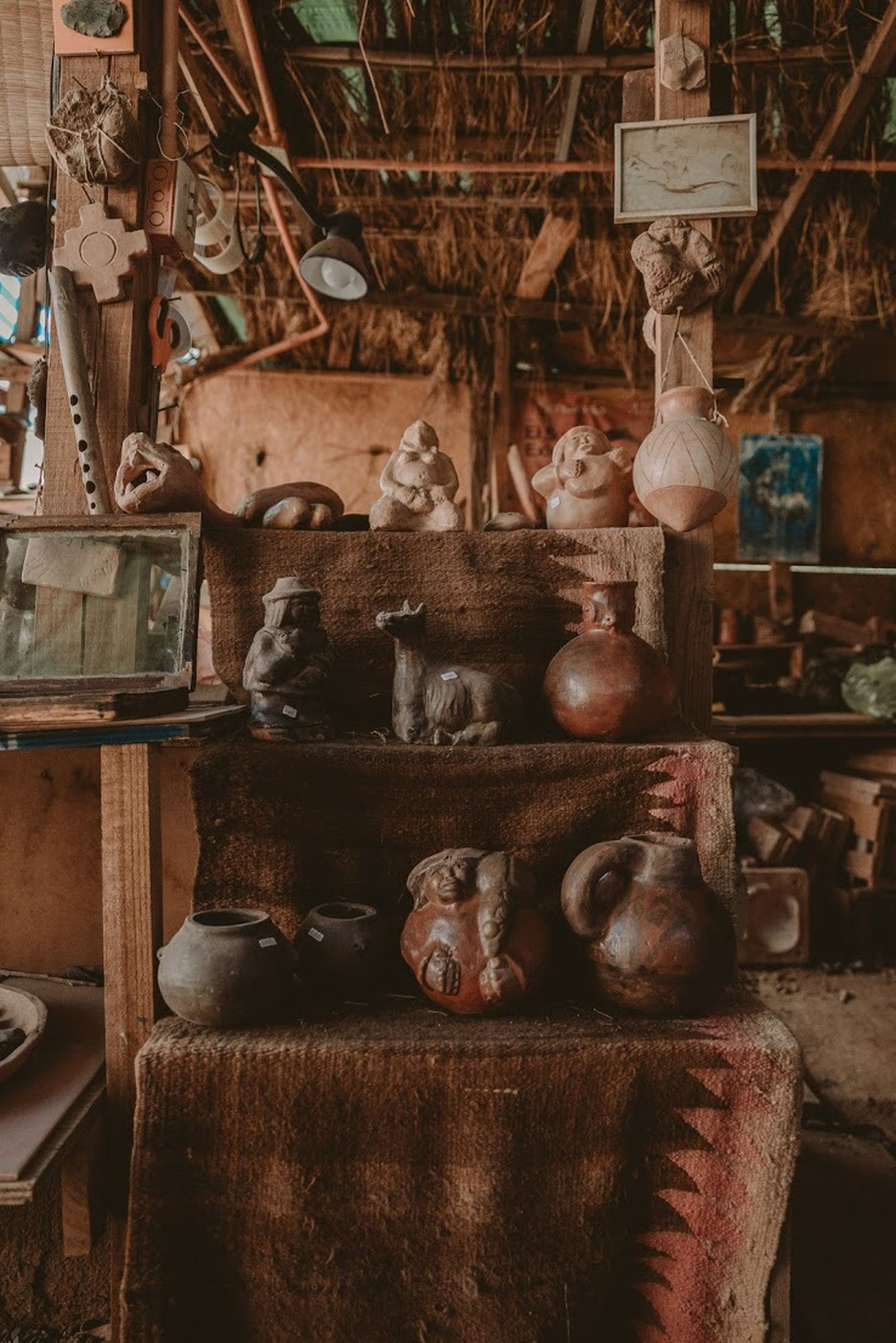 indoors, large group of objects, old, no people, shelf, wood - material, day, domestic room, art and craft, craft, container, history, workshop, group of objects, run-down, the past, abundance, human representation, deterioration, antique