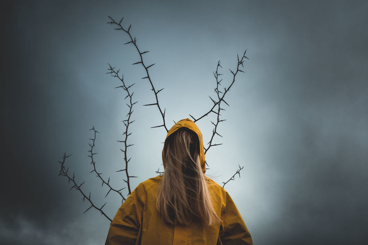 Girl with long hair in yellow hood,  tree with thorns, depression, mysticism, dark thoughts