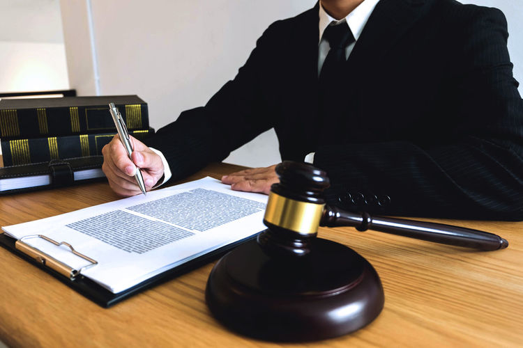 Midsection of judge working at desk in office