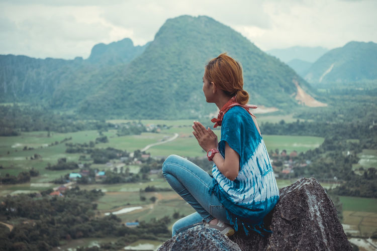 Side view of mid adult woman sitting on cliff against mountains