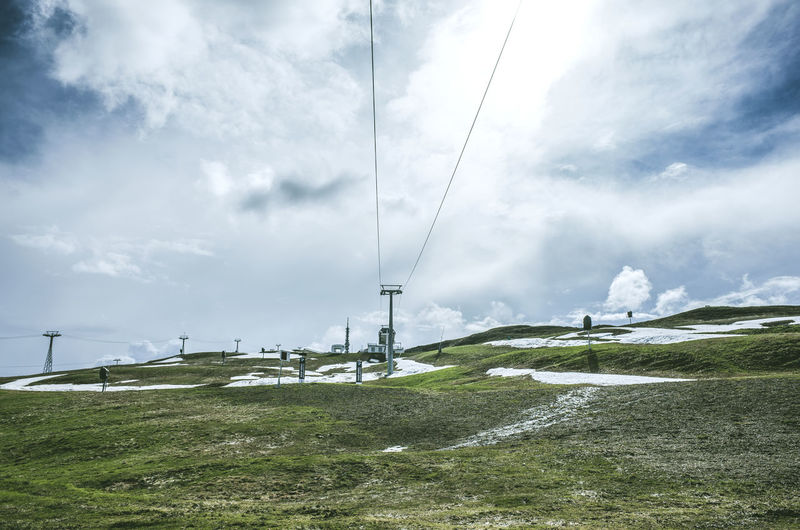 Low angle view of overhead cable car on grassy hill against cloudy sky