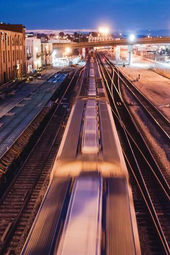 Railroad tracks against illuminated sky at night
