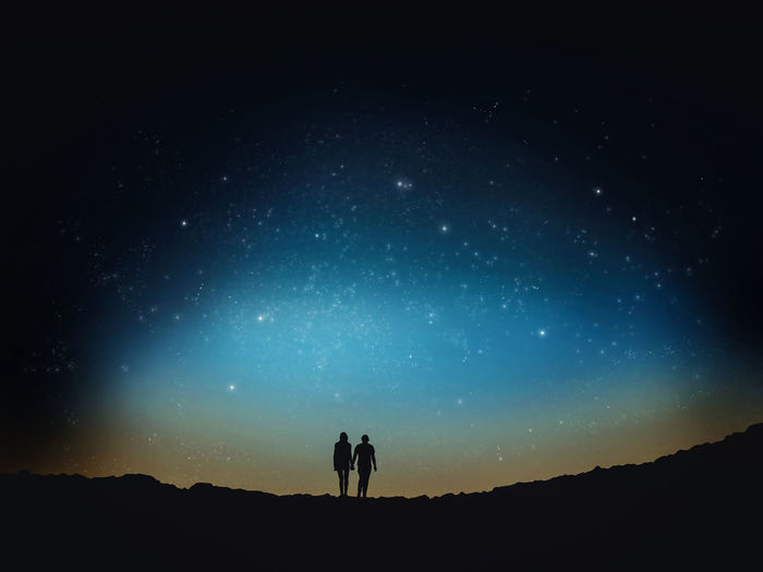 Low angle view of silhouette man and woman walking on field against sky at night