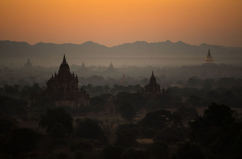 Stupas against mountains during sunset