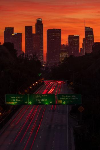 Illuminated street amidst buildings in city against orange sky