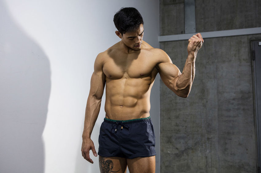 Muscular male fitness model posing behind a grey wall looking at his biceps. Adult Asian  Athlete Body & Fitness Human Body Man Nam Vo Shirtless Sportsman Clenched Fists Fitness Model Grey Wall Handsome Head Down Hunk Male Medium Shot Muscle Muscular Build One Person Shorts Strong Studio Shot Tatoo Torso