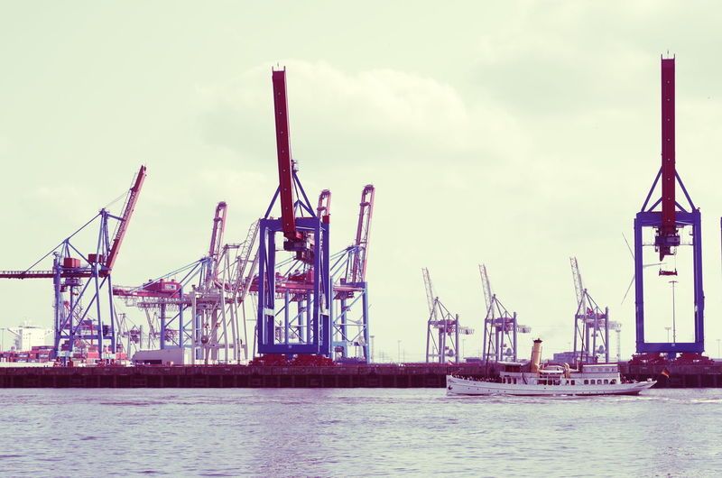 Calm sea with cranes against the sky
