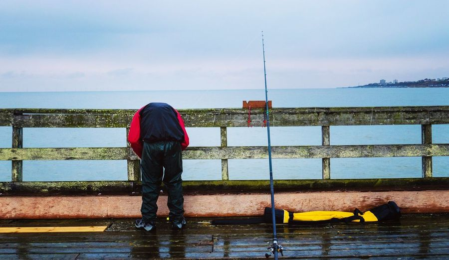 Rear View Of Man Bending On Pier Over Sea Against Sky