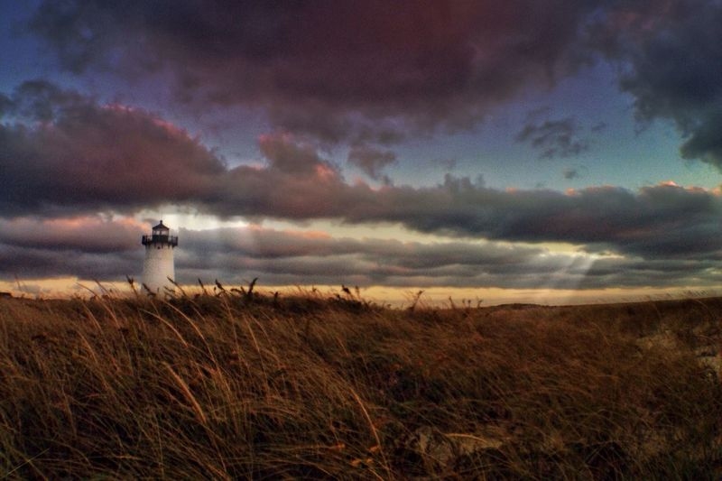 Lighthouse on grassy field against sky during sunset