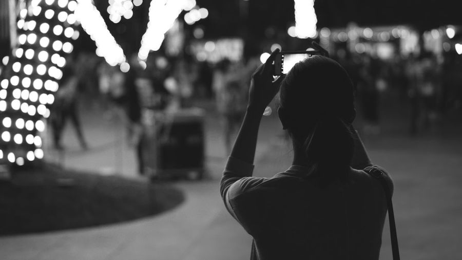 Rear View Of Woman Taking Picture At Night
