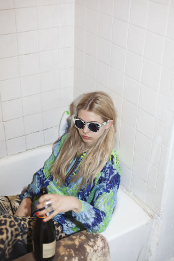 Young woman wearing sunglasses against wall