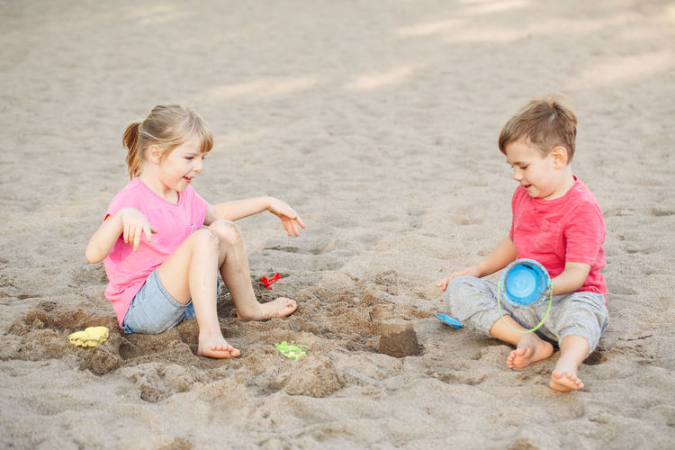 Siblings playing on sand at beach