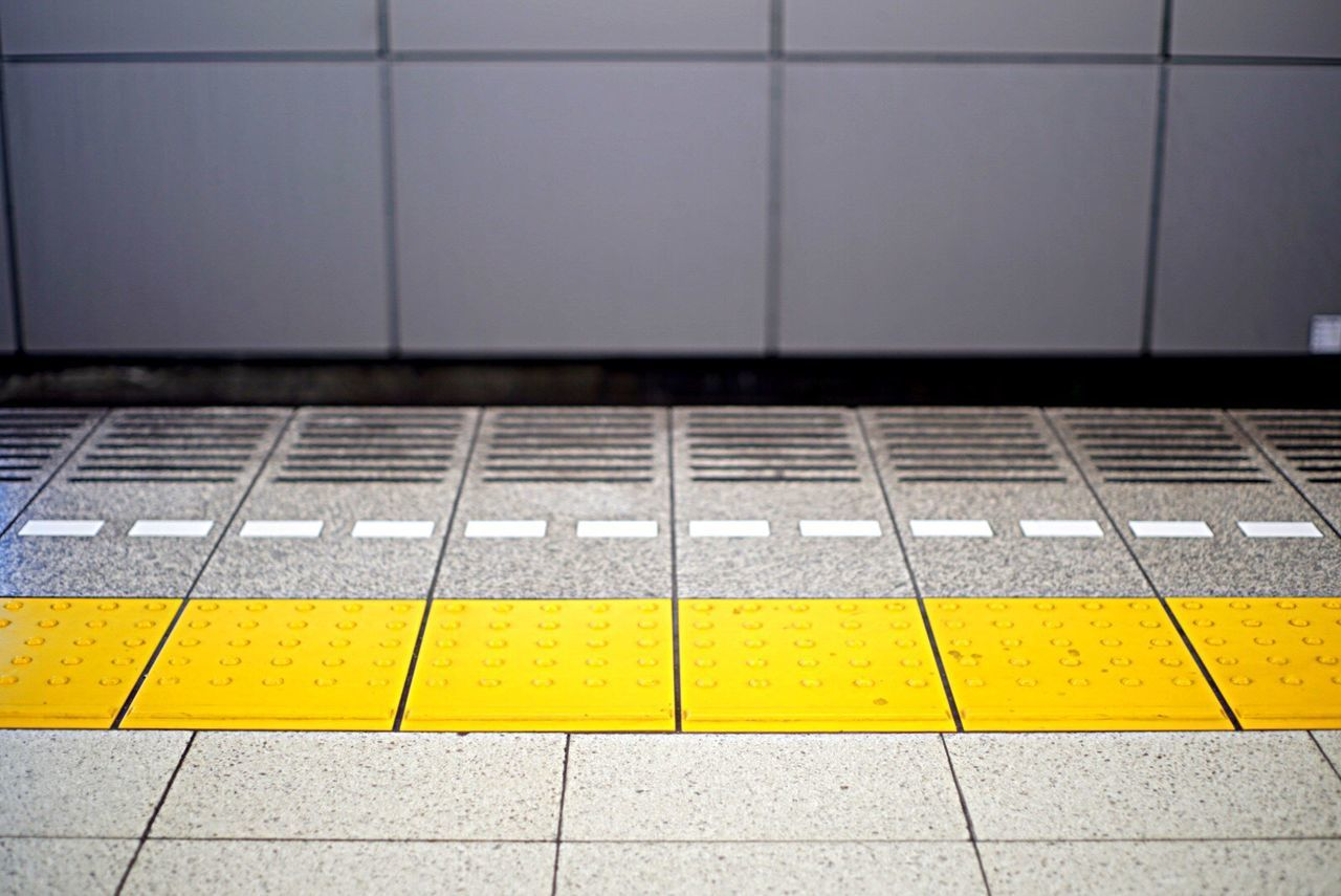 yellow, tiled floor, metal, tile, communication, no people, railroad station platform, indoors, day, technology, close-up