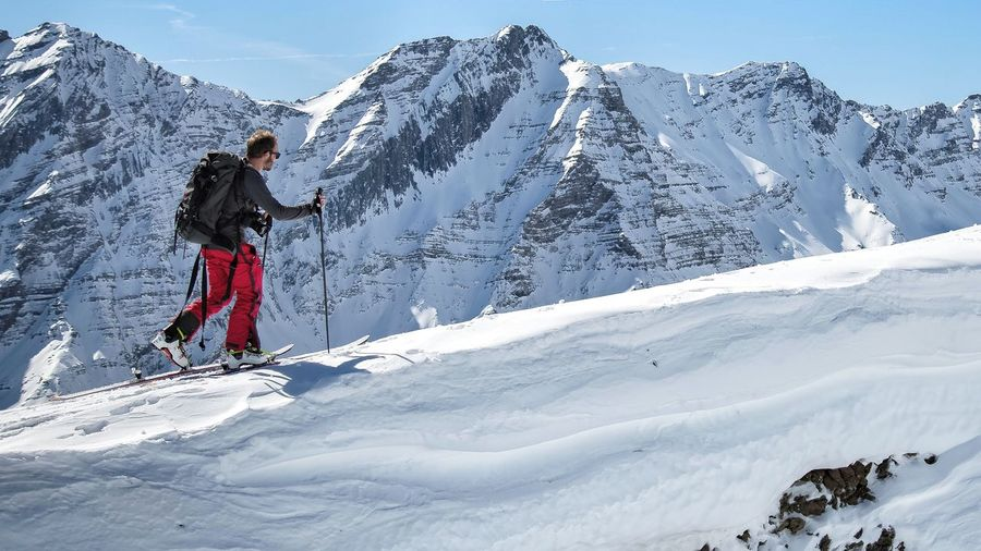Side view of man skiing on snowcapped mountain