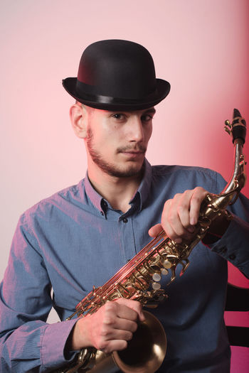 Portrait Of Saxophonist Wearing Hat Against Wall