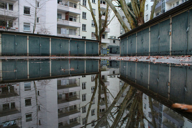 Reflection of buildings in puddle on lake