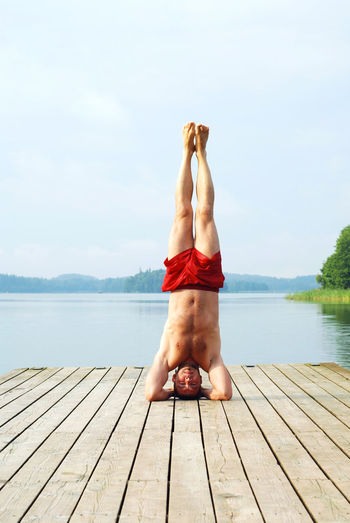 Shirtless man performing headstand on pier against lake