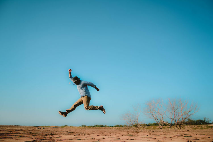 Man jumping on field against sky