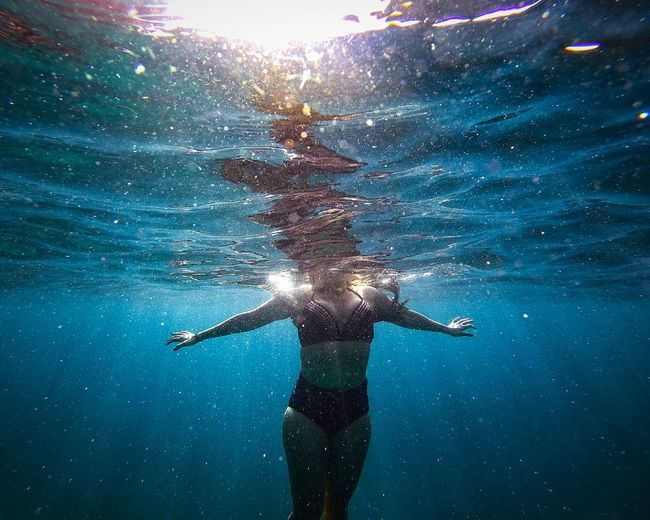 Midsection of young woman swimming in sea