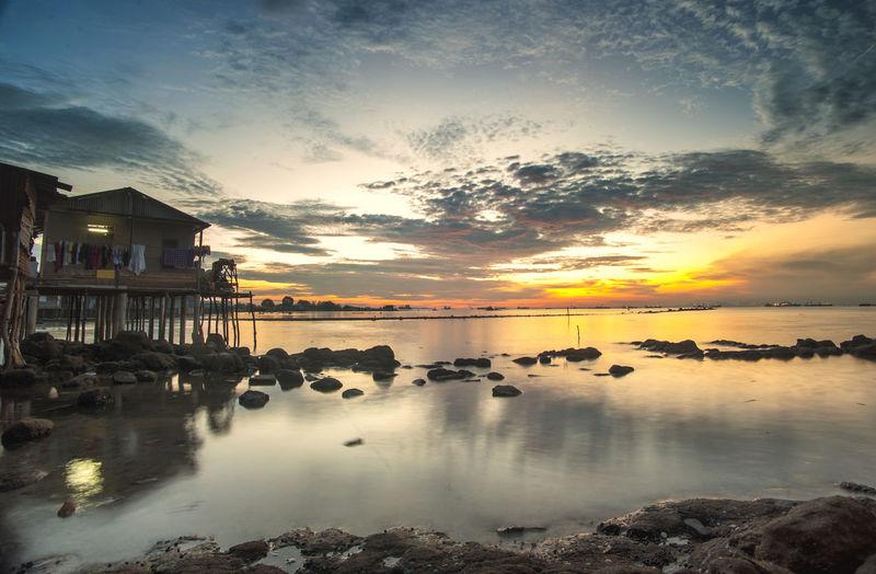 Stilt houses and rocks on sea during sunset