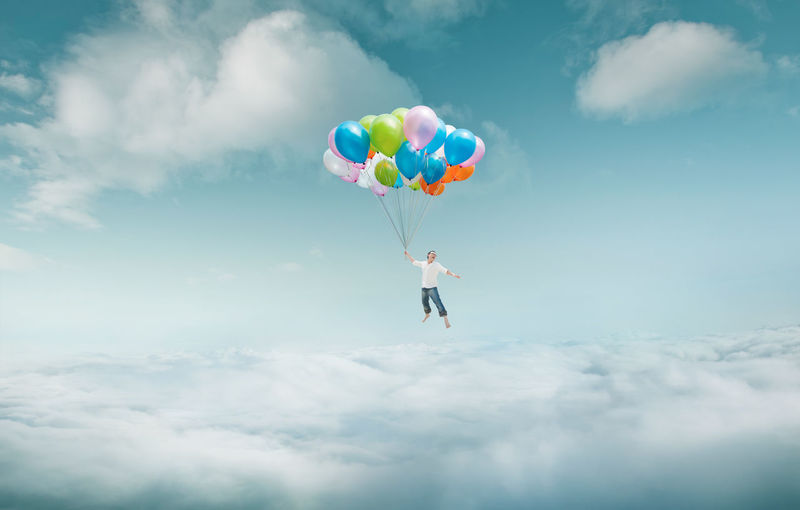 Men floating in sky with bunch of colorful balloons . Balloon Childhood Cloud - Sky Day Energetic Flying Full Length Helium Balloon Leisure Activity Low Angle View Mid-air Multi Colored Nature One Person Outdoors People Real People Sky