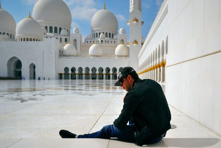 Rear view of man sitting against sheikh zayed mosque