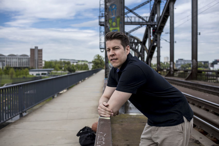 Man standing on a bridge in Frankfurt near railway tracks. City Khaki Pants Man Profile Railing Standing Bridge Caucasian Ethnicity Causal Clothing Clouds Day Golf Shirt Good Looking Handsome Leaning Looking Away From Camera Male Medium Group Of People Outside Posing Railway Track Sky Summer Tall Urban Adventures In The City